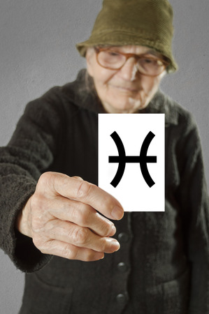 foretelling: Elderly woman holding card with printed horoscope Pisces sign. Selective focus on card and fingers.