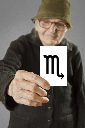 foretelling: Elderly woman holding card with printed horoscope Scorpio sign. Selective focus on card and fingers.