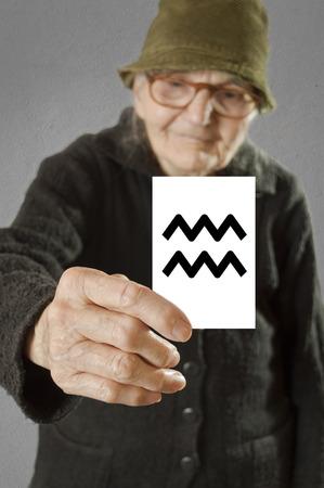인쇄 별자리 물병 자리 기호 노인 여성의 지주 카드. 카드와 손가락에 선택적 초점입니다. 스톡 사진