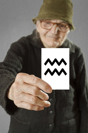 Elderly woman holding card with printed horoscope Aquarius sign. Selective focus on card and fingers.