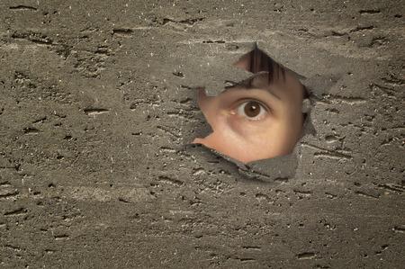 Eye looking through a hole in wall.
