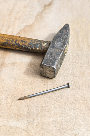 Hammer and nail on wooden board. Selective focus on hammer.
