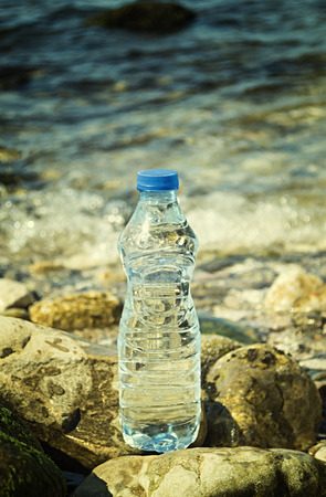 Bottle of the fresh water on the beach of the sea. Shallow depth of field.