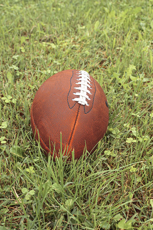 American football ball on a grass.