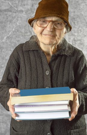 Elderly woman holding stack of books.  Stock Photo