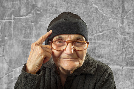 Elderly woman has an idea, pointing with finger on her head. photo