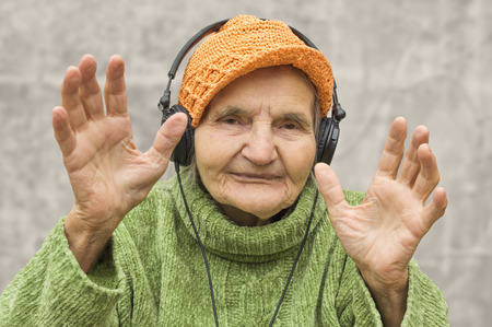 Elderly woman with headphones listening to music.