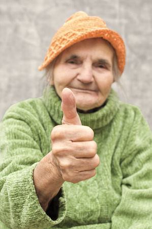 Elderly woman showing thumb up as endorsement or approval gesture. photo