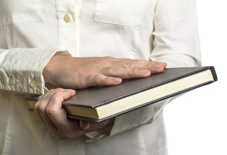 Woman holding black diary with leather hardcover over white background. Reading and student college concept.