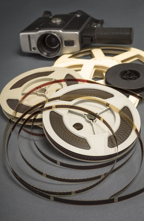 cine: Still life of 8mm cine film reels and old movie camera. Shallow depth of field.