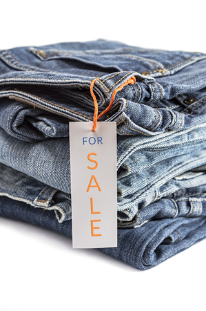 Pile of blue jeans with label isolated on white background. Selective focus on tag label. photo