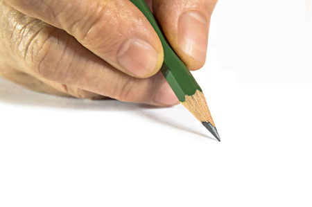 Hand with pencil writing something on white background