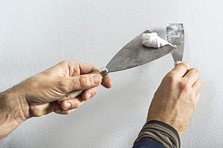 Worker with putty knife working on apartment wall filling Stock Photo