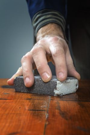 Handyman working with sandpaper on a wooden board.