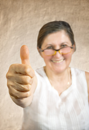 Happy woman showing thumb up.Approval or endorsement concept. Shallow DOF - finger in focus. Stock Photo