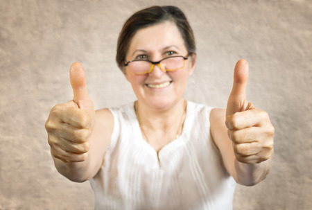 endorsement: Happy woman showing thumb up.Approval or endorsement concept. Shallow DOF - finger in focus. Stock Photo