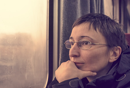 Portrait of worried woman in train. Thinking and wondering concepts.