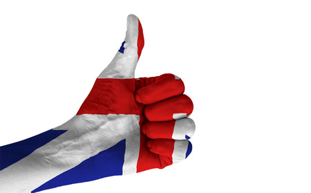 Hand with thumb up gesture in colored United Kingdom national flag isolated on white background. photo
