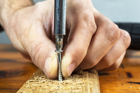 carpenter tools: Close up of a carpenter screwed a hinge on a wooden plank Stock Photo