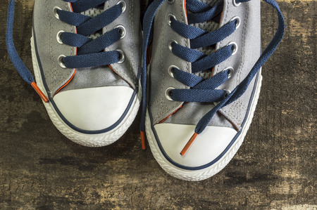 trampled: Sneakers on an old wooden surface. Sports shoes