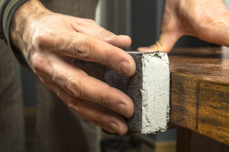 Handyman working with sandpaper on a wooden table