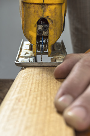woodworker: Woodworker cutting a piece of wood using a electric jigsaw