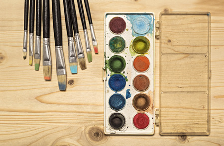 Messy used watercolor paint box and paint brush on wooden table