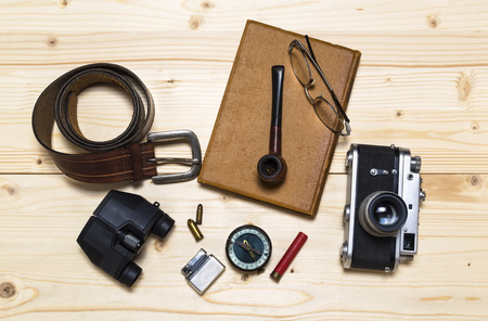 bullet camera: Still life with retro object. Book with compact old camera compass cigarette lighter bullet belt glasses pipe binocular on wood table.