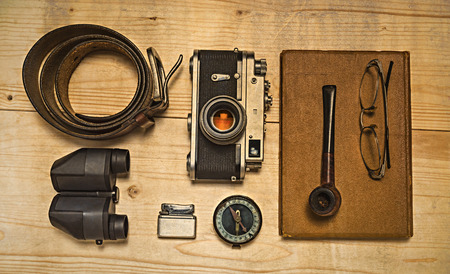 Stil: Still life with retro object. Book with compact old camera compass cigarette lighter belt glasses pipe binocular on wood table.