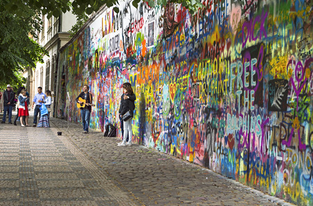 john lennon: PRAGUE, CZECH REPUBLIC - May 21, 2015: John Lennon Wall with unidentified people in Prague. Since the 80s the wall has been filled with Lennon graffiti and lyrics from Beatles songs on Kampa Island Editorial
