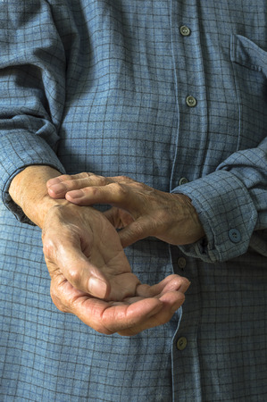 pulsating: Elderly hand measuring her own arm pulse. Selective focus