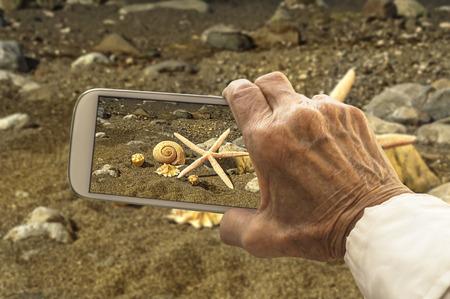 mano anziano: Vecchia mano prende una foto di conchiglie e stelle marine del mare su smart phone. Messa a fuoco selettiva.