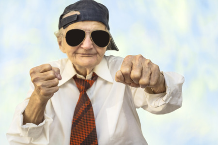 Funny elderly woman wearing cap in a fight pose. Selective focus.