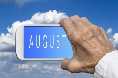 mano anziano: Smart phone in old hand with month of the year - August on screen. Selective focus. Archivio Fotografico