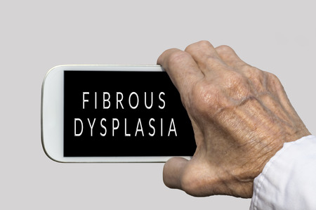 radiation therapy: Smart phone in old hand with FIBROUS DYSPLASIA text on screen. Selective focus Stock Photo