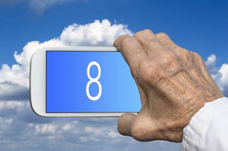 mano anziano: Smart phone in old hand with number EIGHT on screen. Selective focus