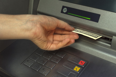 Receiving: Person receiving money from the ATM.Selective focus. Stock Photo