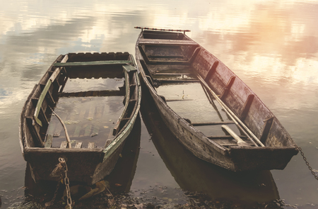 lost lake: Old flooded wooden boats on river. Selective focus.