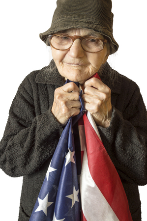 old flag: Senior woman holding an American flag, selective focus.