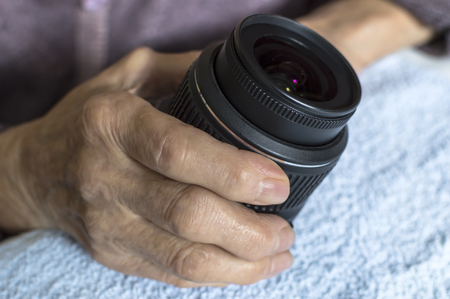 DSLR lens in old womans hands. Selective focus.