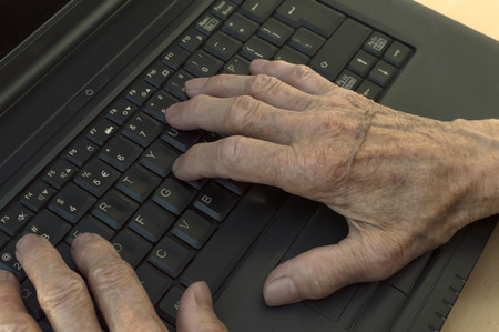 global retirement: Closeup on elderly hands on keyboard of laptop. Selective focus.