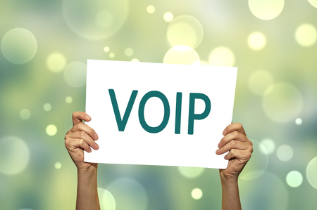 voip: VOIP voice over internet protocol card in hand with abstract light background. Selective focus.
