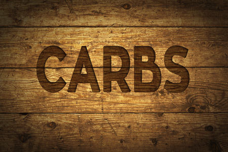Grunge wood with text Carbs. Stock Photo