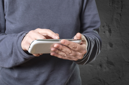 communicator: Hands holding smartphone. Selective focus.