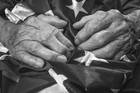 old flag: Old womans hands holding an American flag. Black and white image. Selective focus.