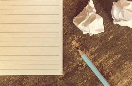 Top view of pencil notepad and crumpled paper on wooden table. Selective focus.
