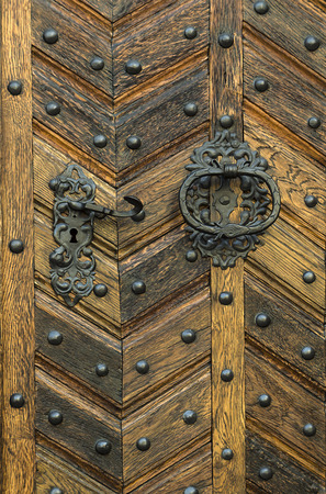 door handle: Old wooden entrance door with antique door handle