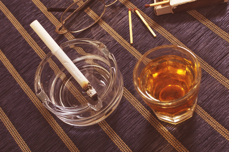 Glass of whiskey and cigarette in ashtray.