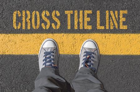 Zapatillas de deporte de pie sobre la línea amarilla. Cruzando la línea concepto. Foto de archivo