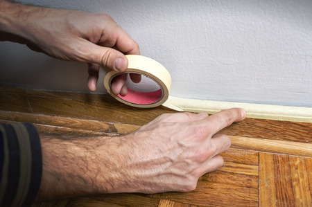 priming paint: Worker protecting batten moulding with masking tape before painting at home improvement work. Stock Photo